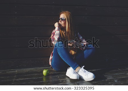 Portrait of a young university female student holding cell telephone while relaxing after lectures, smiling beautiful women with trendy look using mobile phone while enjoying good day in the fresh air - stock photo