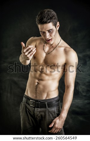Portrait of a Young Vampire Man Shirtless, Showing his Torso, Chest and Abs, Gesturing to Camera, Looking at the Camera, on Dark Background. - stock photo