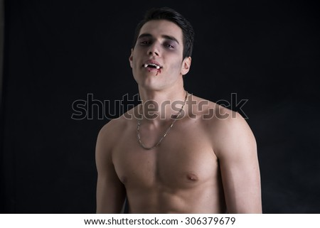 Portrait of a Young Vampire Man Shirtless, Showing his Torso, Chest and Abs, Looking at the Camera, on Dark Background. - stock photo