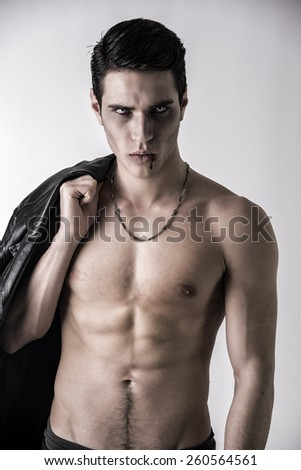 Portrait of a Young Vampire Man with Black Leather Jacket, Showing his Torso,  Chest and Abs, Looking at the Camera, on a White Background. - stock photo