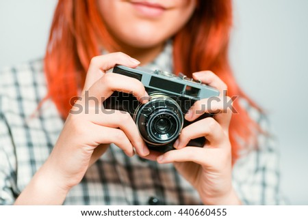Portrait of a young woman adjusts retro camera redhead with glasses, isolated on a gray background - stock photo