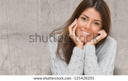 Portrait Of A Young Woman against a concrete wall - stock photo