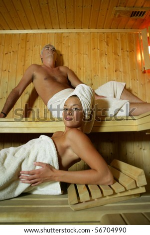 Portrait of a young woman and a man in a sauna - stock photo