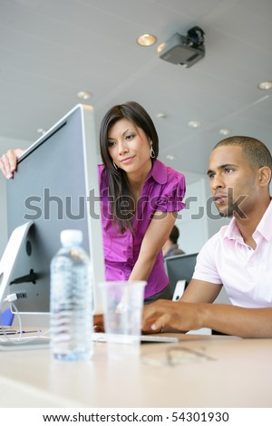 Portrait of a young woman and a young man in front of a desktop computer - stock photo