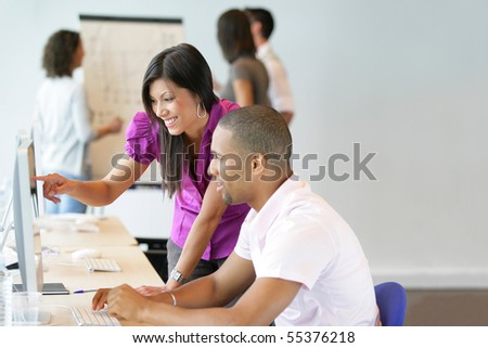 Portrait of a young woman and a young man sitting in front of a desktop computer - stock photo