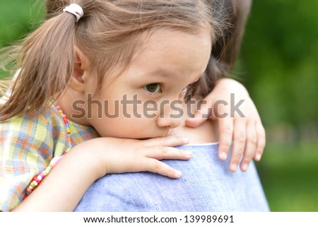 portrait of a young woman and her daughter in late spring outside - stock photo