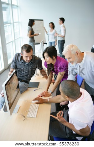 Portrait of a young woman and men in front of a desktop computer - stock photo