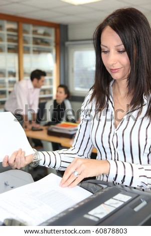 Portrait of a young woman at the copier - stock photo