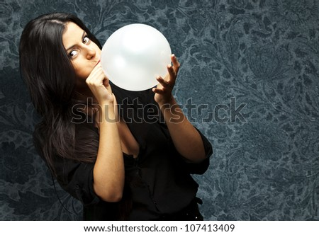portrait of a young woman blowing a balloon against a vintage background
