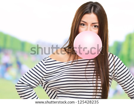Portrait Of A Young Woman Blowing Bubblegum at a park - stock photo