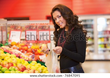 Portrait of a young woman buying fruits in the supermarket - stock photo