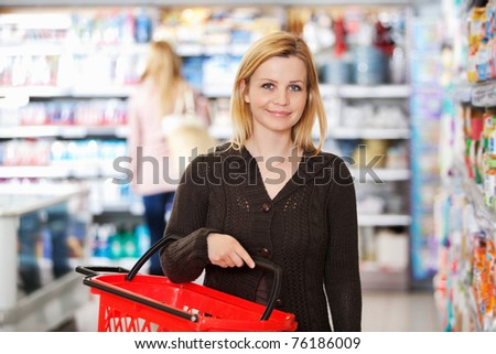 Portrait of a young woman carrying basket while shopping in the supermarket - stock photo