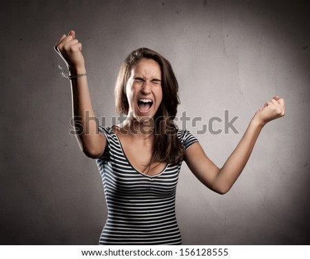 portrait of a young woman celebrating being a winner - stock photo