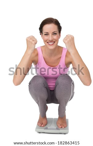 Portrait of a young woman cheering on weight scale over white background - stock photo