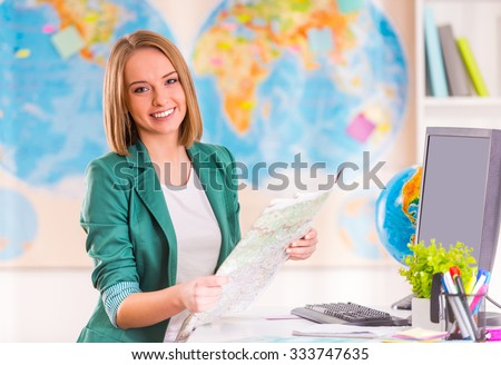 Portrait of a young woman chooses a place to travel using map sitting in office travel agency - stock photo