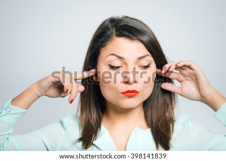 Portrait of a young woman closes hands over her ears, she does not want to listen to