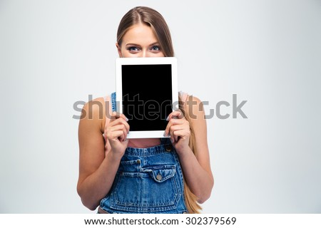 Portrait of a young woman covering her face with tablet computer isolated on a white background - stock photo
