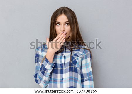 Portrait of a young woman covering her mouth with palm and looking away over gray background - stock photo