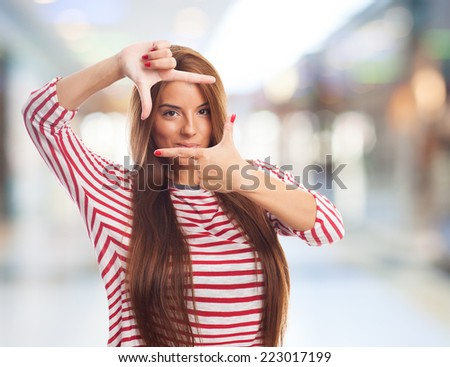 portrait of a young woman doing a frame gesture - stock photo