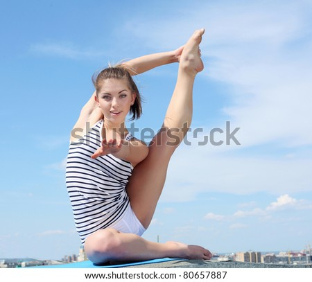 Portrait of a young woman doing exercises against blue sky - stock photo