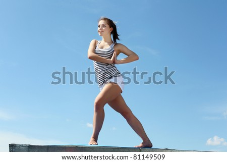 Portrait of a young woman doing exercises against blue sky