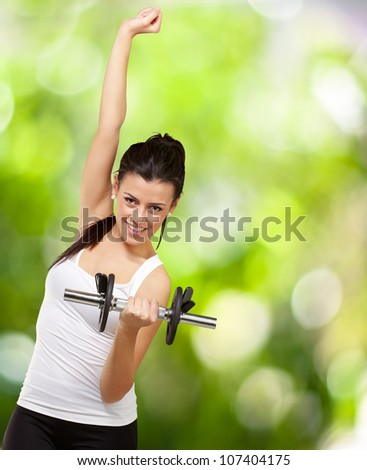 portrait of a young woman doing fitness with weights over a nature background - stock photo
