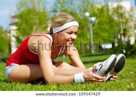 Portrait of a young woman doing physical exercise outdoors - stock photo