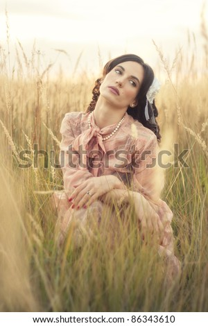 Portrait of a young woman dressed in retro clothes, sitting in a field of tall grass. - stock photo