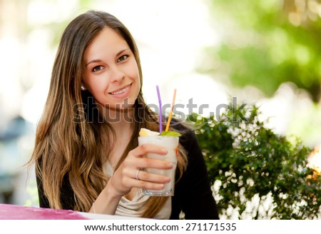 Portrait of a young woman drinking a cocktail - stock photo
