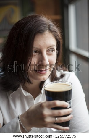 Portrait of a young woman drinking a pint of stout beer.