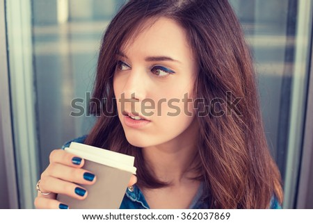 Portrait of a young woman drinking coffee outdoors holding paper cup - stock photo