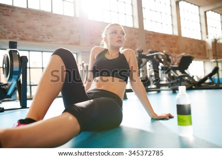 Portrait of a young woman during a break in the gym. Caucasian female sitting on floor looking away, resting after workout. - stock photo