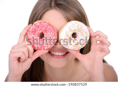 Portrait of a young woman eating a cake against a white background - stock photo