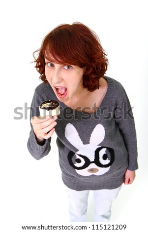 Portrait of a young woman eating a cake isolated on white background - stock photo