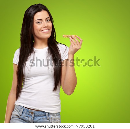 portrait of a young woman eating a cereal bar over a green background - stock photo