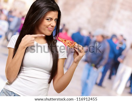 Portrait Of A Young Woman Eating A Piece Of Pizza, Outdoor - stock photo