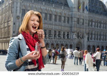 Portrait of a young woman eating chocolate on Grand place in Brussels - stock photo