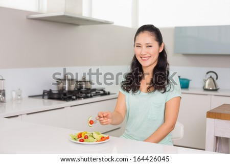 Portrait of a young woman eating salad in the kitchen at home