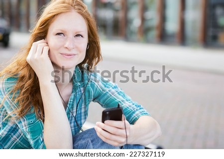 Portrait of a young woman enjoying a casual moment in a city as she listens to music on a mobile phone. - stock photo