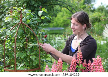 Portrait of a young woman enjoying som flowers in thegarden - stock photo