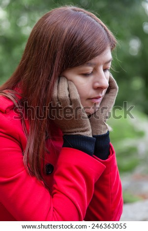 Portrait of a young woman feeling depressed sitting on a forest wearing a red overcoat during winter  - stock photo