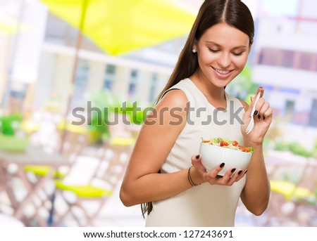 Portrait Of A Young Woman Having a Salad, outdoor - stock photo