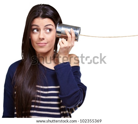 portrait of a young woman hearing through a tin can over a white background - stock photo