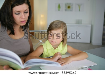 Portrait of a young woman helping a little girl in doing her homework - stock photo
