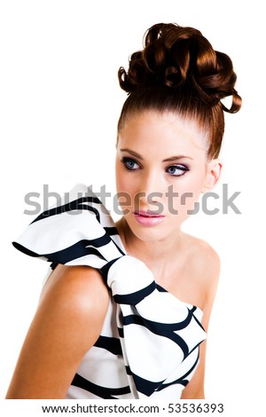 Portrait of a young woman. Her hair is styled in an updo and she is wearing a black and white dress with a large bow on the shoulder. Vertical shot. Isolated on white.