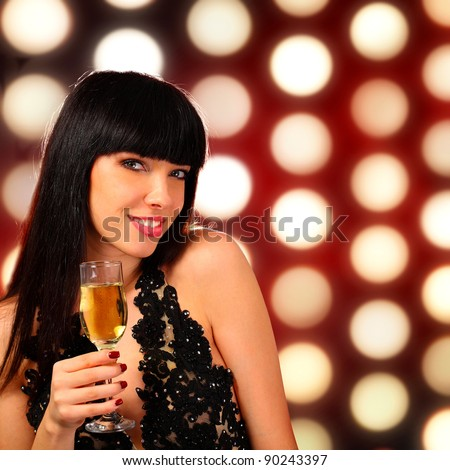 Portrait of a young woman holding a champagne glass - stock photo