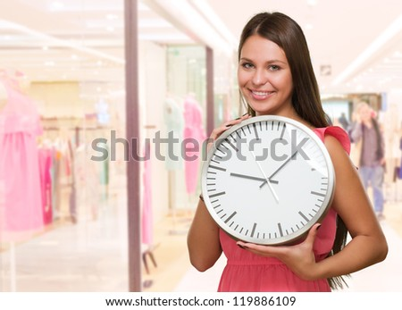 Portrait Of A Young Woman Holding A Clock at a mall - stock photo