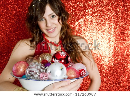 Portrait of a young woman holding a dish full of Christmas bar balls and smiling while standing in front of a red glitter background.