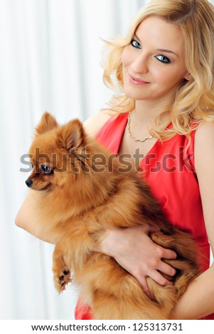 Portrait of a young woman, holding a dog, smiling