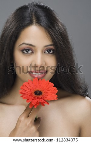 Portrait of a young woman holding a flower - stock photo